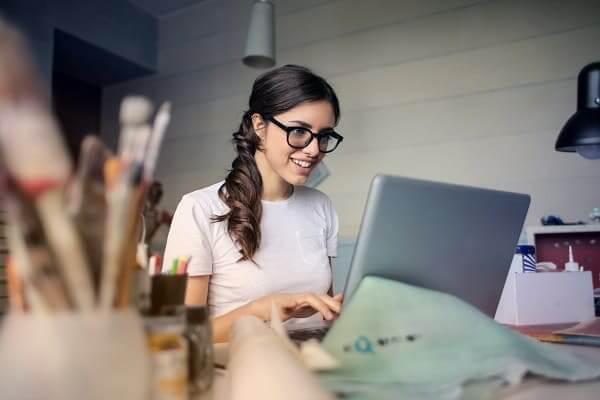 Frau, die zu Hause mit PC arbeitet